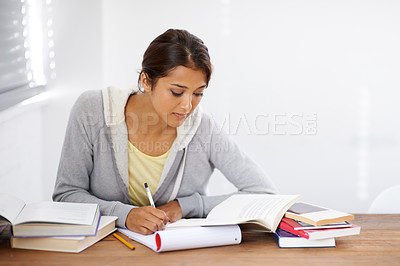 Buy stock photo A pretty college student taking notes from her textbook in her dorm room