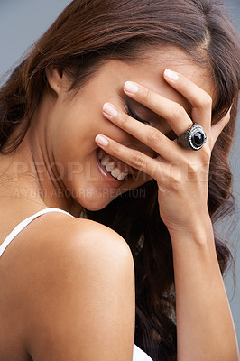 Buy stock photo A laughing woman with her face being covered by her hand