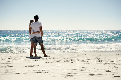 Buy stock photo A back view of a couple looking at the ocean on the beach