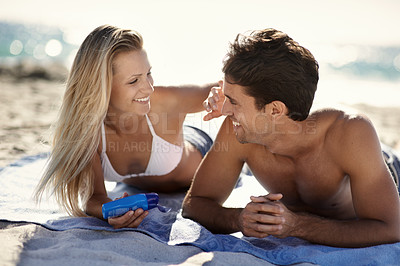 Buy stock photo A woman putting sunblock on her boyfriend's nose while they lay on the beach