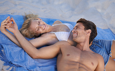 Buy stock photo A young couple lying together on a towel at the beach