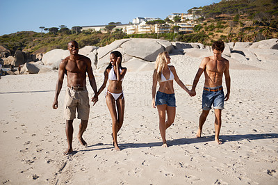 Buy stock photo Two young couples walking on the beach together