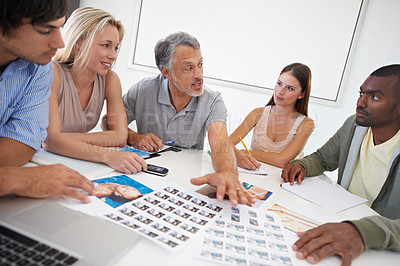 Buy stock photo A group of designers discussing image choices