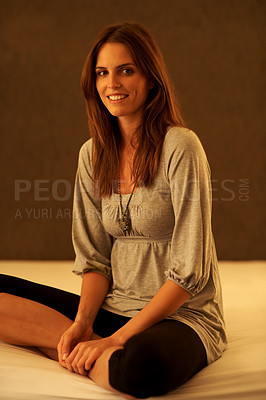 Buy stock photo Young woman sitting against brown background
