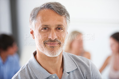 Buy stock photo Portrait of a handsome mature man sitting in the boardroom with his colleagues