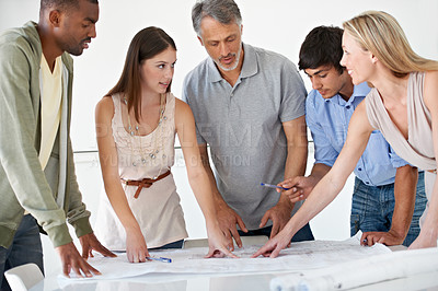 Buy stock photo A team of architects brainstorming in the boardroom over a set of blueprints