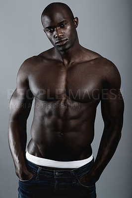Buy stock photo A handsome and muscular young man posing in the studio