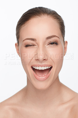 Buy stock photo A beautiful young woman winking playfully at the camera