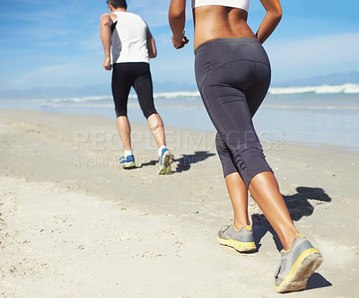 Buy stock photo Cropped shot of two people running on the beach