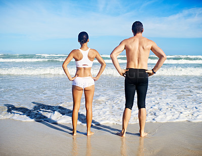 Buy stock photo A man and woman standing with their hands on their hips in front of the sea