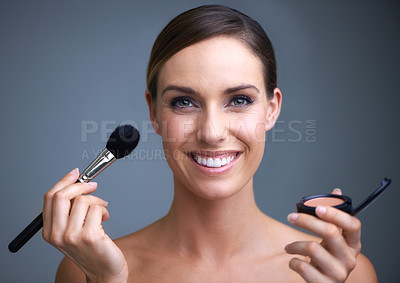 Buy stock photo Portrait of an attractive young woman holding blusher and a brush