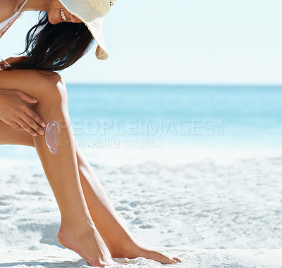 Buy stock photo Cropped view of a young woman putting sun cream on her legs