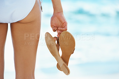 Buy stock photo A back view of a woman's bottom in a bikini while she holds a pair of sandals