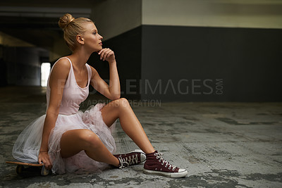 Buy stock photo A young ballerina sitting on a skateboard wearing sneakers