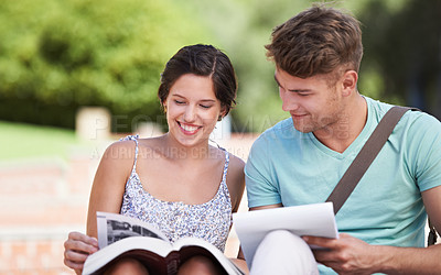 Buy stock photo A young couple in college sitting together and studying in the park