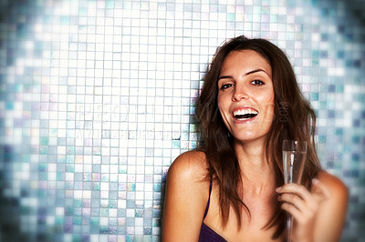Buy stock photo Portrait of a laughing young woman smiling at the camera while holding up a glass of champagne