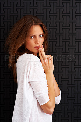 Buy stock photo Cute young woman posing against dark background