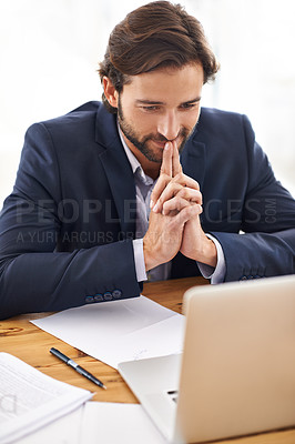Buy stock photo A handsome businessman thinking while working on his laptop