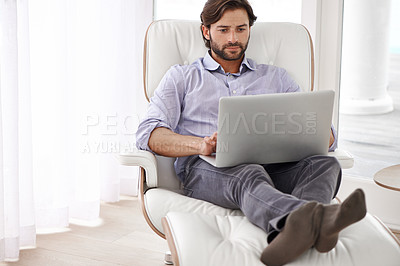Buy stock photo A handsome businessman  relaxing on his chair while working on his laptop