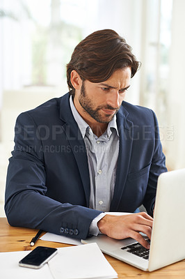 Buy stock photo An attractive businessman typing on his laptop