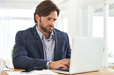 Buy stock photo An attractive businessman hard at work on his laptop
