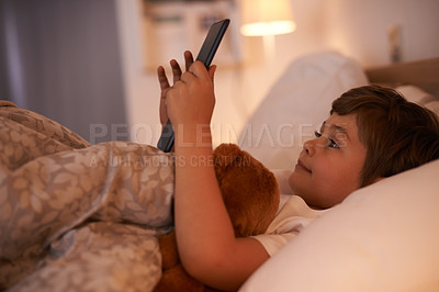 Buy stock photo Shot of a young boy playing on a tablet while lying in bed