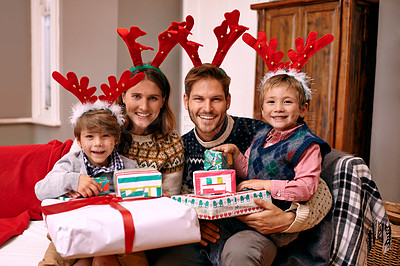 Buy stock photo Shot of a family wearing reindeer antlers while enjoying themselves at Christmas