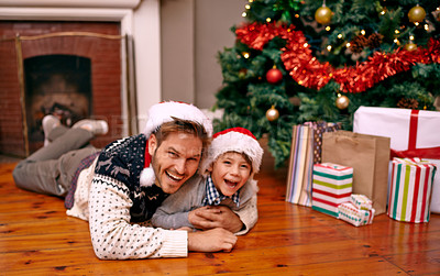 Buy stock photo A young boy and his father lying on the floor next to a Christmas tree