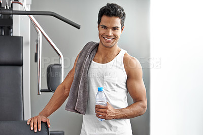 Buy stock photo A young ethnic man standing by an exercise machine at the gym