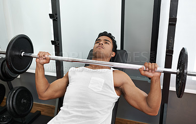 Buy stock photo A young ethnic man lifting a heavy barbell