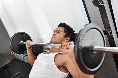 Buy stock photo A young ethnic man lifting weights at the gym