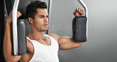 Buy stock photo A fitness shot of an athletic young man using an exercise machine