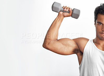 Buy stock photo A fitness shot of a muscular young man lifting a dumbbell