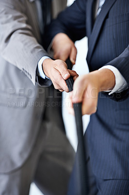 Buy stock photo Closeup studio shot of two businessmen in suits pulling a rope