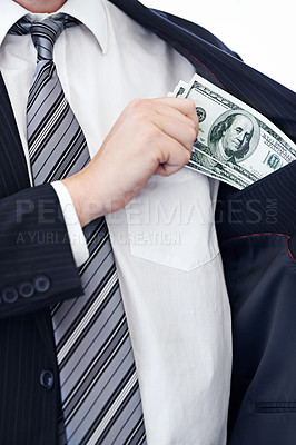Buy stock photo Cropped shot of a businessman placing money into his pocket