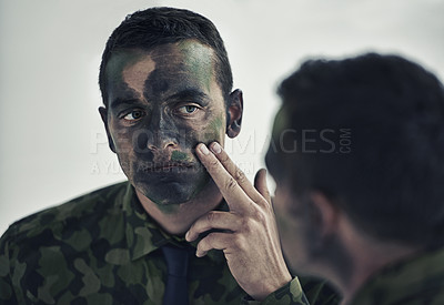 Buy stock photo A young military examining his camouflaged face in the mirror