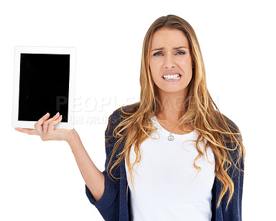 Buy stock photo A young woman looking displeased as she holds a tablet