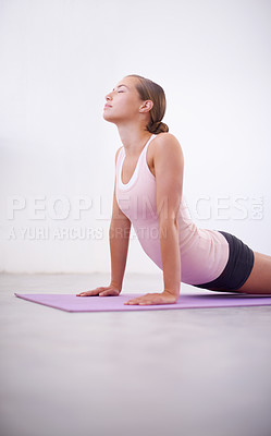 Buy stock photo An attractive young woman in a cobra position