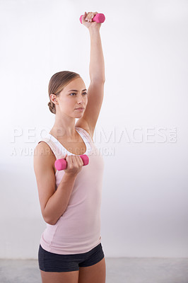 Buy stock photo An attractive young woman working out with weights
