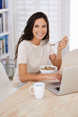 Buy stock photo Portrait of an attractive young woman using her laptop at home while eating breakfast
