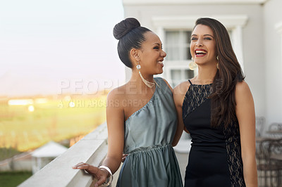 Buy stock photo Two young women in evening wear standing on a balcony