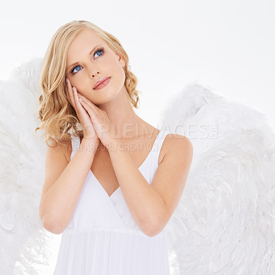 Buy stock photo Studio shot of a young woman in angel wings isolated on white