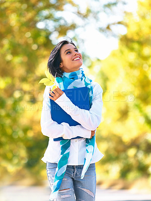 Buy stock photo A young woman strolling down the street admiring the autumn leaves