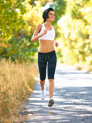 Buy stock photo A happy woman jogging down the street