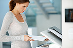 Attractive young woman photocopying at the office