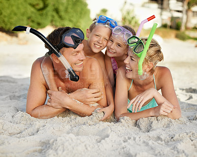Buy stock photo A family in snorkeling gear lying on the sand at the beach