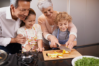 Buy stock photo Group shot of a brother and sister bonding with their grandparents in the kitchen