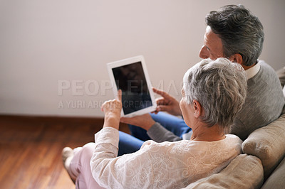 Buy stock photo A senior couple relaxing on the sofa with their digital tablet