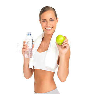Buy stock photo Portrait of a sporty young woman holding an apple and a bottle of water against a white background
