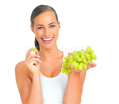 Buy stock photo Cropped portrait of an attractive young woman eating a bunch of grapes